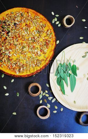 Delicious pumpkin pie sprinkle with pumpkin seeds on the black Desk and the decor of sage leaves top view closeup.