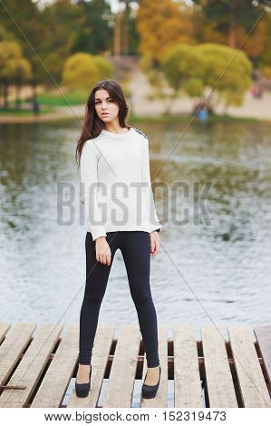 Slender long-haired brunette in a white jumper black leggings and shoes standing on a wooden bridge near the river in the autumn Park.