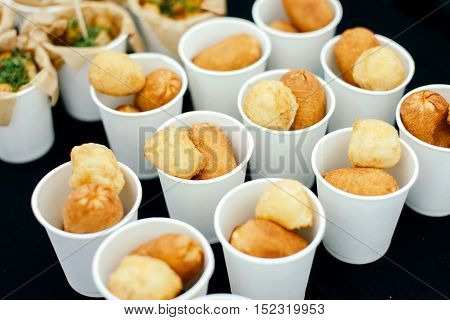 Chicken nuggets in paper cups. Side view against the black table.