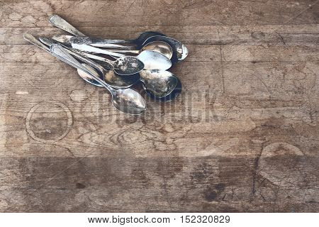 Stacked pile of tarnished silver spoons against rustic wooden table top