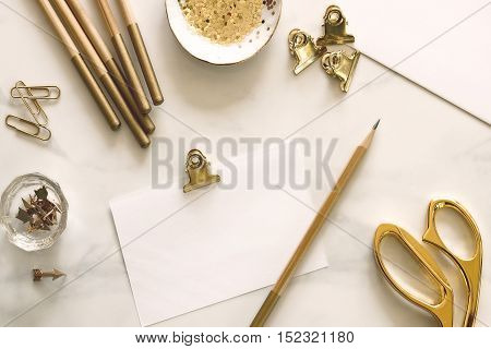 Over head flat lay desktop with gold office supplies and blank notecard for text or copy