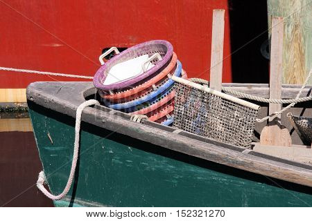 Small wooden skiff filled with empty baskets after off-loading its catch at the dock.