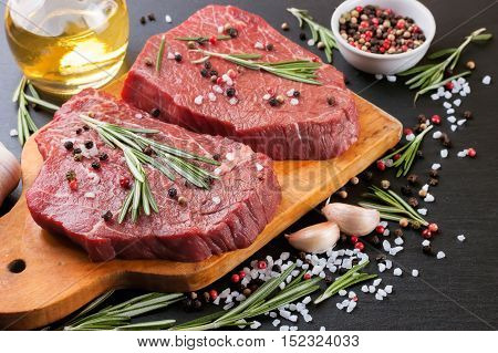 Raw beef steak with spices and ingredients for cooking on cutting borard and slate background.