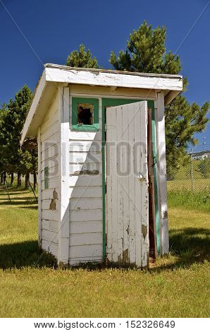 Old outhouse with open door and ventilation window to the front
