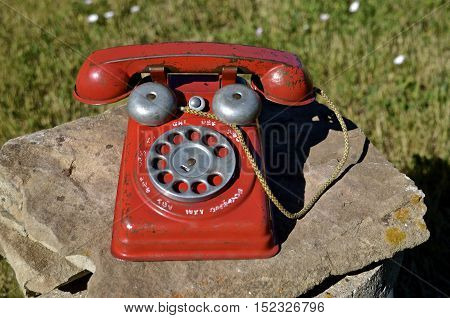 An old toy child's dial telephone left on a rock outside.