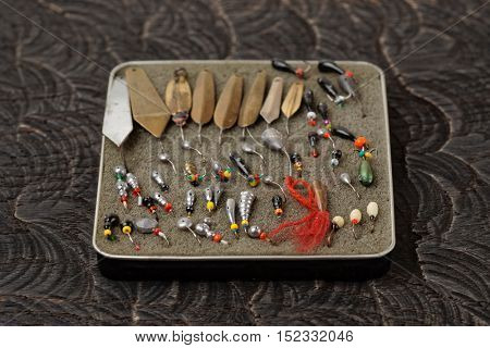 Set of lures for ice fishing on black wooden surface