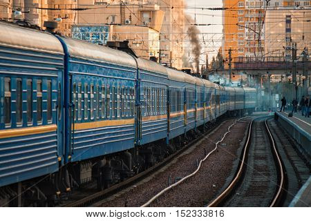 The big old train is going on ukrainian railways. City buildings are on background.People are waiting on platform - Odessa railway station. The city is on background