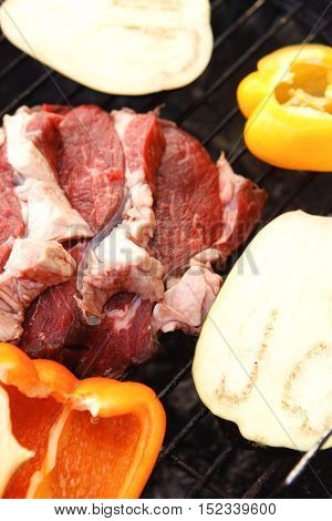 fresh raw beef fillet with vegetables on charcoal bbq grill ready to prepare