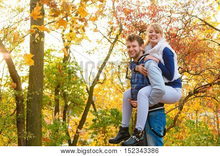 Man Giving Piggyback Ride To Woman In Park