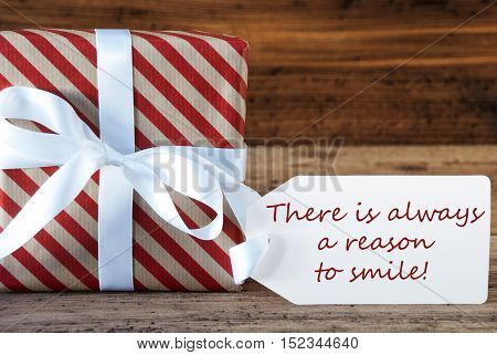 Macro Of Christmas Gift Or Present On Wooden Background. Card For Seasons Greetings, Best Wishes Or Congratulations. White Ribbon With Bow. English Quote There Is Always A Reason To Smile