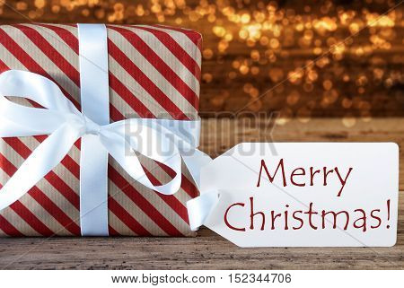 Macro Of Christmas Gift Or Present On Atmospheric Wooden Background. Card For Seasons Greetings, Best Wishes Or Congratulations. White Ribbon With Bow. English Text Merry Christmas