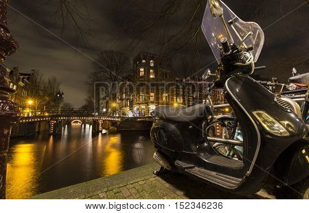 A nightscape in the Amsterdam city center, showing canals lit by streetlights, apartments and scooter parked on the pavement lining the canal.