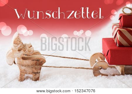 Moose Is Drawing A Sled With Red Gifts Or Presents In Snow. Christmas Card For Seasons Greetings. Red Christmassy Background With Bokeh Effect. German Text Wunschzettel Means Wish List