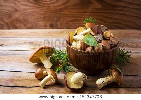 Edible mushrooms in the wooden bowl. Fresh forest picking mushrooms on the rustic table.