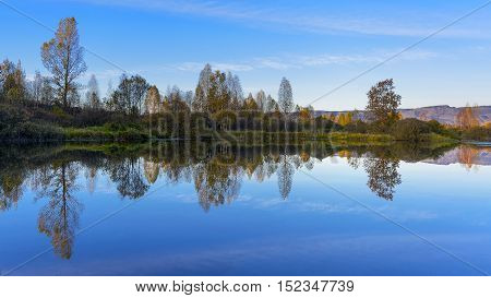 River landscape with multicolored fall trees. Fall idyllic river landscape. Beautiful autumn day on the tranquil river.