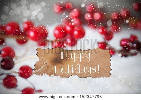 Burnt Label With English Text Happy Holidays. Red Christmas Decoration On Snow. Cement Wall As Background With Bokeh Effect And Snowflakes. Card For Seasons Greetings