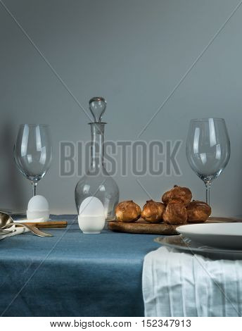 still life. old damask, glasses, buns on the table with a blue tablecloth
