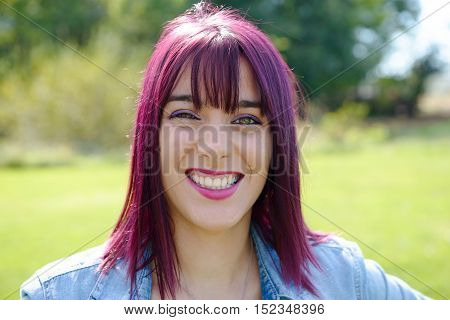 portrait of a young woman with green eyes and red hairs outdoors