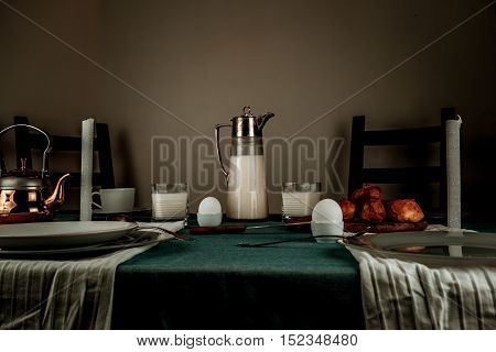 still life. milk jug, candles, tea, eggs bread rolls on the table