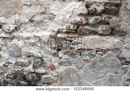Ancient stone wall cracked and pieces of plaster