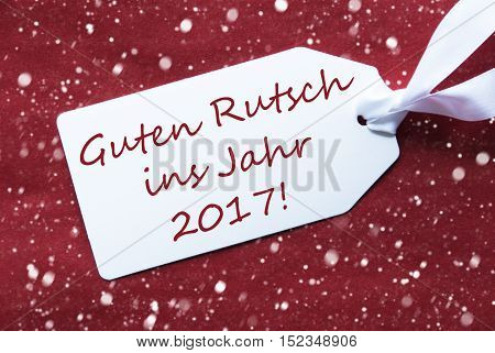 One White Label On A Red Textured Background. Tag With Ribbon And Snowflakes. German Text Guten Rutsch Ins Jahr 2017 Means New Year