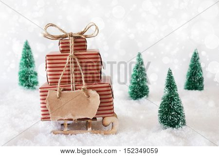 Sleigh Or Sled With Christmas Gifts Or Presents. Snowy Scenery With Snow And Trees. White Twinkling Background With Bokeh Effect. Label With Copy Space For Advertisement Or Free Text