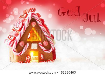 Gingerbread House In Snowy Scenery As Christmas Decoration. Candlelight For Romantic Atmosphere. Red Background With Bokeh Effect. Swedish Text God Jul Means Merry Christmas