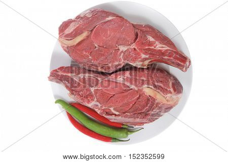 two fresh raw ribeye beef steak on white plate with red and green hot chili pepper isolated over white background rib eye