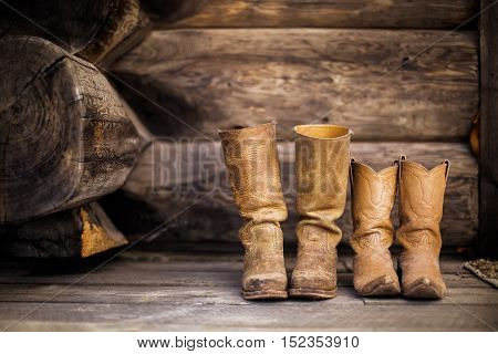 worn tan western boots against hand-carved rustic wooden wall