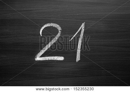 number twenty one enumeration written with a chalk on the blackboard