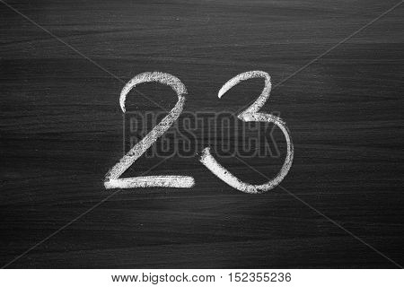 number twenty three enumeration written with a chalk on the blackboard