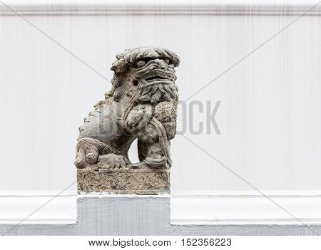 Stone lion statue in the traditional Chinese style of the Thai temple.