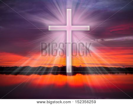 A cross in the sky over a river or coean with light rays at sunrise or sunset.