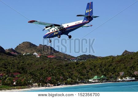 ST. BARTS, FRENCH WEST INDIES - JANUARY 21, 2006: Winair plane landing at St Barts airport. St. Barts is considered a playground of the rich and famous.