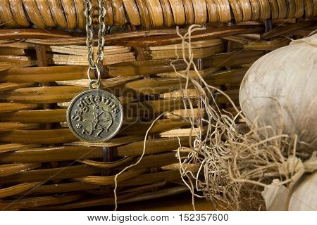 Garlic and zodiac sign on a background of a wicker basket