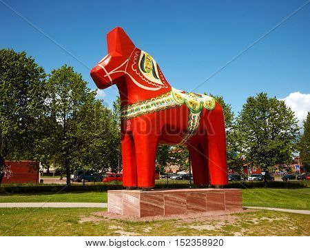 Mora, Sweden - June 7, 2012: A large public wooden sculpture of a traditional dalecarlian horse traditionally painted and decorated located in the Swedish town Mora. The dalecarlian horse is a symbol of the province of Dalarna in Sweden.
