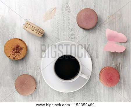 A photo of a cup of coffee with various pastel coloured macarons and a pink paper butterfly