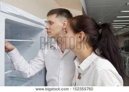 Happy family couple looking at large fridges in the store