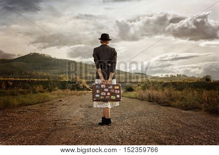 Women with vintage travel suitcase at old road. Photo in old image style