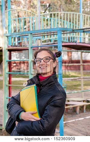 Girl in glasses with notebooks smiling and looking up
