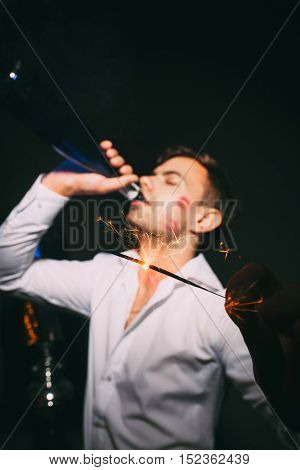 Young attractive man in white shirt drinking from bottle and holding sparkler on the foreground. Adult with red lipstick on his cheek at after party.