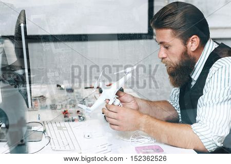 Bearded repairman disassembling drone, double exposure. Working day at electronic toy repair shop