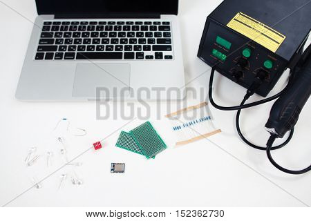 Electronic engineer workplace with components. Top view on laptop, multimeter, breadboard and set of small transmitters. Technology, development, construction concept