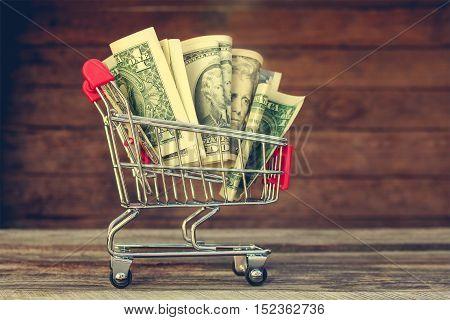 Shopping cart with money on old wood background. Toned image