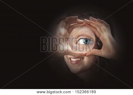 Female eye looking through magnifying glass close up in a black background