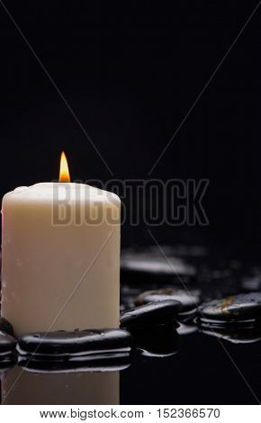 white candle and therapy stones