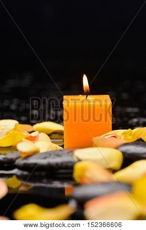 rose petals with yellow candle and therapy stones