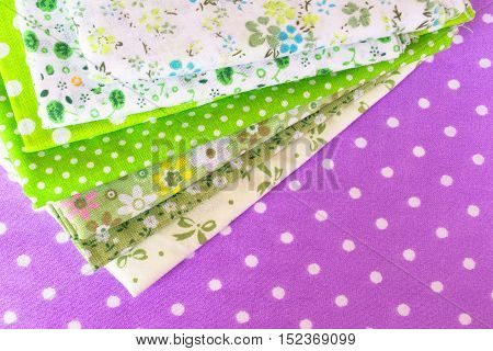 Green fabric set on purple background. Fabric with flower pattern