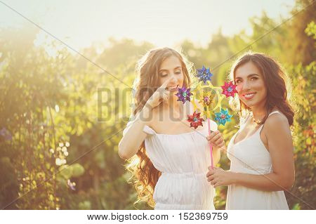 Two sisters with windmill. Girls at sunset. Portrait of a warm toning. Family relationships.