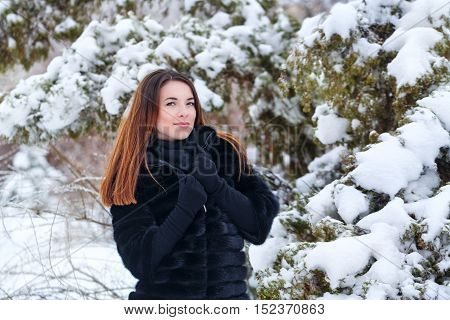 Sweet attractive girl in a fur coat and gloves in the winter park.